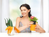 Housewife with flower in pot and gardening set — Stok fotoğraf
