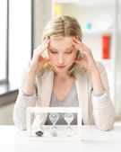 Tired woman behind the table with hourgalss — Stock Photo