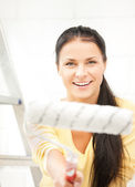 Happy young woman with paintroller — Stock Photo