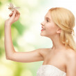 Woman with dragonfly in hand — Stock Photo #23349246