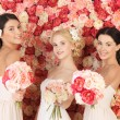 Three women with background full of roses — Stock Photo #23386848