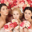 Three women with background full of roses — Stock Photo #23386974