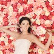 Woman with bouquet and background full of roses — Stock Photo #23386980