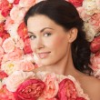 Woman with background full of roses — Stock Photo #23387044