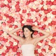 Young woman with background full of roses — Stock Photo #23387066