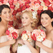 Stock Photo: Three women with background full of roses