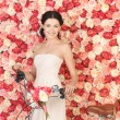 Woman with bicycle and background full of roses — Stock Photo #23387268