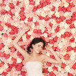 Young woman with background full of roses — Stock Photo #23387566