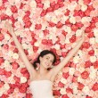 Young woman with background full of roses — Stock Photo #23387570