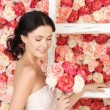 Woman with old ladder and background full of roses — Stock Photo