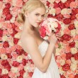Woman with bouquet and background full of roses — Stock Photo #23387744