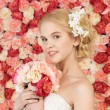 Woman with bouquet and background full of roses — Stock Photo #23387808
