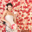 Woman with bicycle and background full of roses - Stockfoto