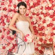 Woman with bicycle and background full of roses — Stock fotografie