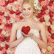 Woman with heart and background full of roses — Stock Photo #23387942