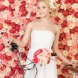 Woman with bicycle and background full of roses — Stock Photo