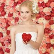 Woman with heart and background full of roses - Stock Photo