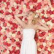 Young woman with background full of roses - Stockfoto