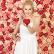 Woman with heart and background full of roses — Stock Photo
