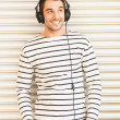 Man in casual clothes with headphones - Stock Photo