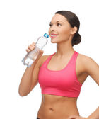Sporty woman drinking water from bottle — Stock Photo