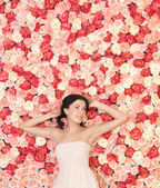 Young woman with background full of roses — Stockfoto
