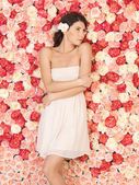 Young woman with background full of roses — Foto de Stock