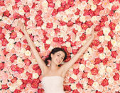 Young woman with background full of roses — Stock Photo