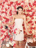 Woman with bicycle and background full of roses — Stockfoto