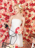 Woman with bicycle and background full of roses — Stok fotoğraf