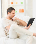 Man sitting on the couch with tablet pc — Stockfoto