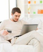 молодой человек с ноутбуком и кредитной карты у себя дома — Стоковое фото