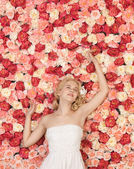 Young woman with background full of roses — Stok fotoğraf