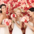 Three women with background full of roses — Stock Photo #23391810