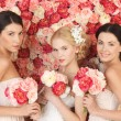 Three women with background full of roses - Stockfoto