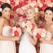 Three women with background full of roses - Stock Photo