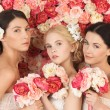 Three women with background full of roses — Stock Photo #23819017