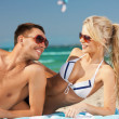 Happy couple in sunglasses on the beach - Stock Photo