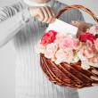 Man holding basket full of flowers and postcard - Stok fotoğraf