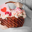 Stock Photo: Man holding basket full of flowers and postcard