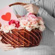 Man holding basket full of flowers and postcard - Stock Photo