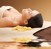 Woman in spa salon lying on the massage desk — Foto de Stock