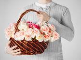 Man holding basket full of flowers — Stock Photo