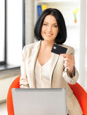 Businesswoman with laptop showing credit card — Stock Photo