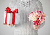 Man holding bouquet of flowers and gift box — Stock Photo