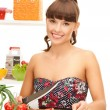 Beautiful woman in the kitchen cutting vegetables — Stock Photo