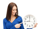 Businesswoman pointing her finger at wall clock — Stock Photo