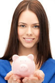 Lovely woman with small piggy bank — Stock Photo
