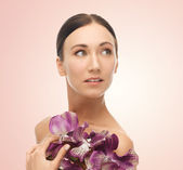 Woman with orhid flowers — Stock Photo