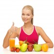 Woman with juice and fruits showing thumbs up — Stock Photo #24011015